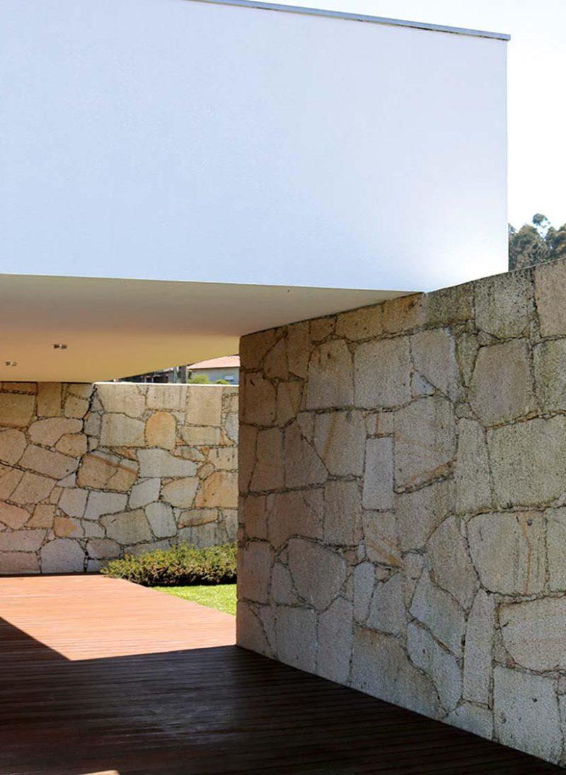 Na casa da Oliveira, o granito amarelo é o elemento que lhe confere distinção, modernidade e elegância. Parede em granito amareli vila real na varanda exterior da sala de estar. Projeto Obraatelier