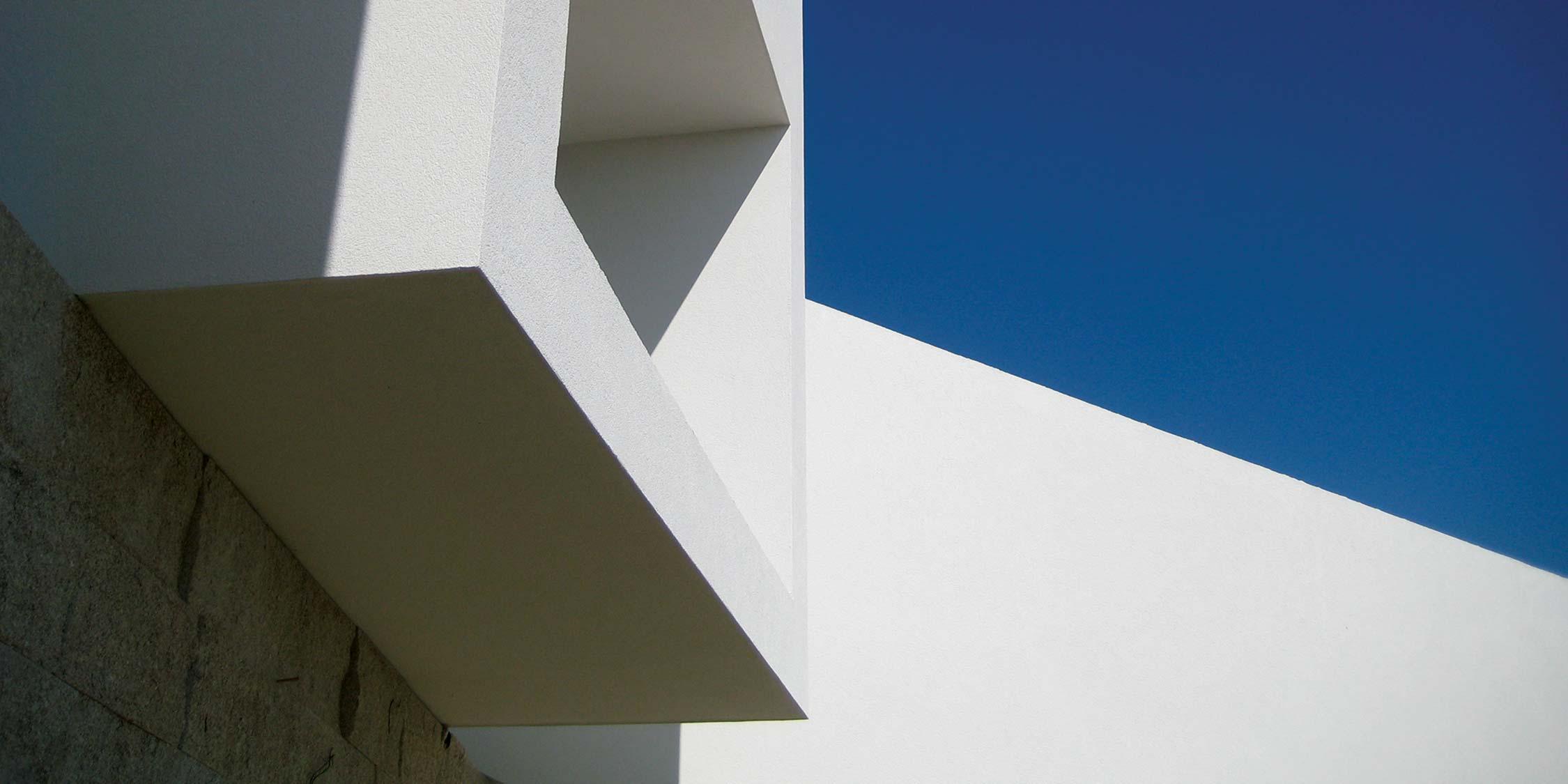 Casa da Vinha Dama, casa inspirada na natureza. Volumes brancos dos quartos sobre a parede em pedra de granito amarelo. Projeto Obra Atelier