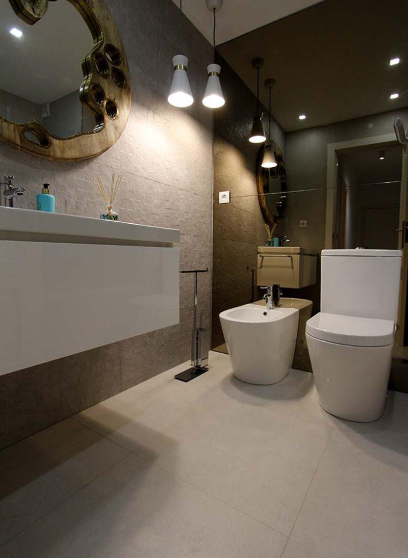 Apart. Cascais. Papel de parede moderno e elegante renova apartamento. Casa de banho de quarto com ceramico texturado e parede com espelho bronze na parede. Projeto interiores Obra Atelier