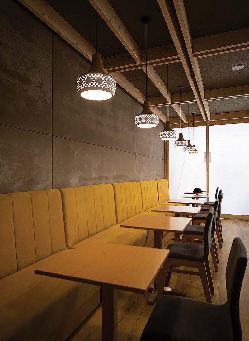 Restaurante Tapas & Snack Bar 25. cor amarela do mobiliario contrasta com o cinza da parede. Reformulação de loja para restaurante de Tapas & Snack Bar, em Serviço chave na mão do Obra Atelier.